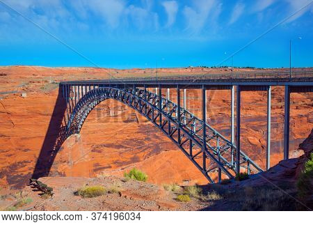 Picturesque red sandstone is the base of the bridge. Arched bridge from one giant steel arch. Glen Canyon Bridge over the Colorado River. The concept of environmental, active and photo tourism