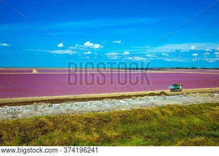 Dark Pink Salt Water Bay. Salt production on the seashore. Huge truck rides along the bay with pink salt water. The Mediterranean coast of France, Camargue. Concept of eco and photo tourism