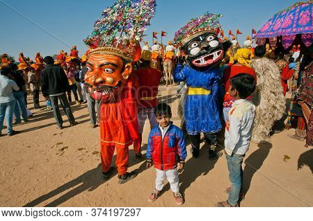 Jaisalmer, India: Scary Colorful Masks Of The Evil Characters Of Hinduism On Carnival Crowd Of Deser
