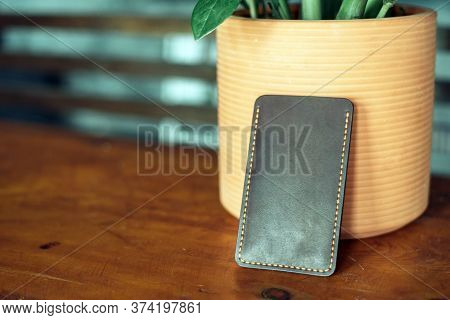 The Black Phone Case Made Of Eco-leather Is Made By A Master. Handmade Phone Case On A Wooden Backgr