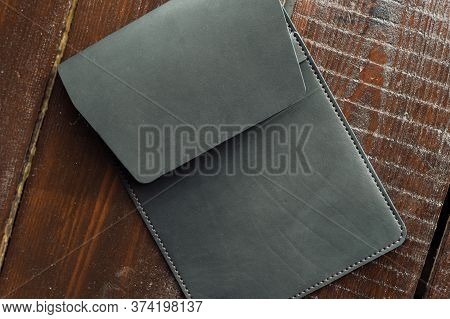 Black Leather Case For Tablet. Eco Leather Case On A Wooden Background.