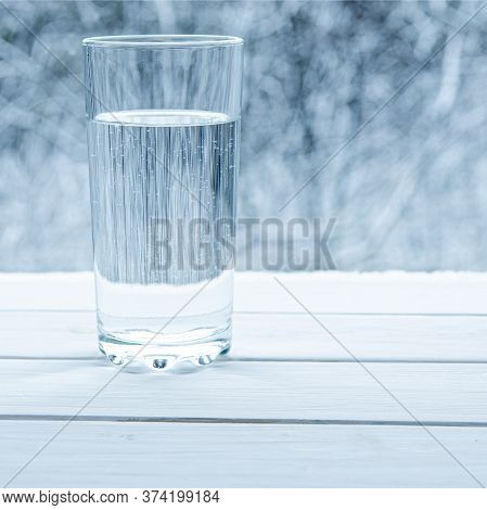 A Glass Of Melted Clean Cold Water Stands On A Wooden Window Sill Against The Background Of The Wint
