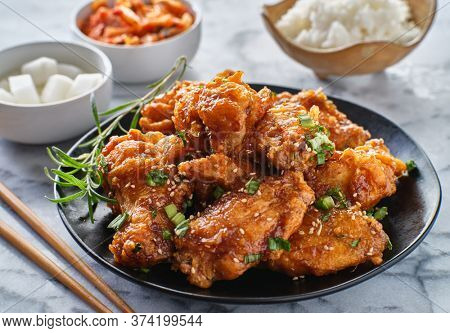 crispy fried korean chicken wings in galbi sauce with pickled radish, kimchi, and rice side dishes