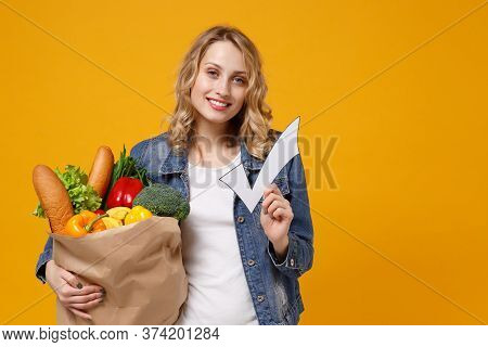 Beautiful Young Girl In Denim Clothes Isolated On Orange Background. Delivery Service From Shop Or R
