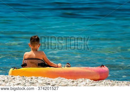 Back View Of Happy Teenage Boy On A Kayak At Azure Lagoon. Children In Kayak At Sea. Active Vacation