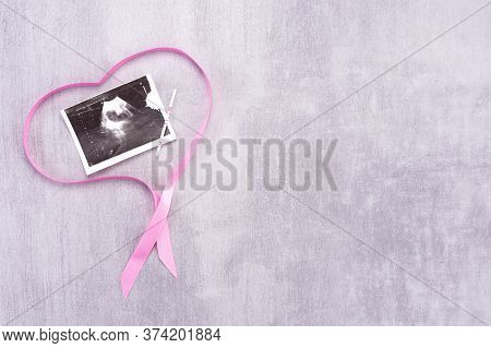 Ultrasound Image Of A Baby With A Pink Ribbon In The Form Of A Heart On A Gray Background With Place