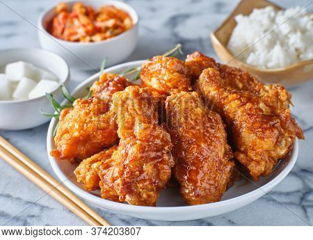 crispy fried korean chicken wings in soy garlic sauce with pickled radish and kimchi sides
