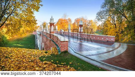 Brick Bridge Over A Ravine In Tsaritsyno Park In Moscow Among Colorful Autumn Trees In The Light Of