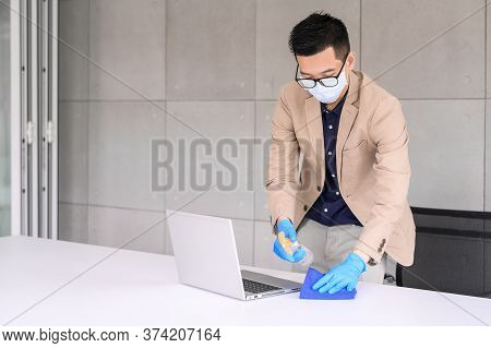 Businessman Wear Face Mask And Glove Using Microfiber Cloth And Alcohol Sanitizer Spray To Clean Lap
