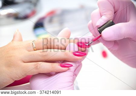 Manicurist Apply Nail Polish. Close-up Of A Woman Applying Nail Polish To Her Finger Nails.pink Nail