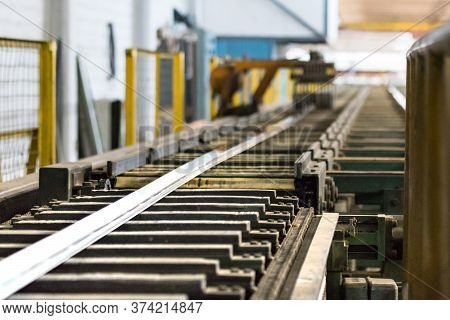An Aluminium Profile On The Puller Stage On An Extrusion Profile Roller Runout Table.
