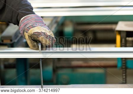 A Man Machine Operator Using Safety Gloves Controlling The Stretch Of An Aluminiun Profile With A Sq