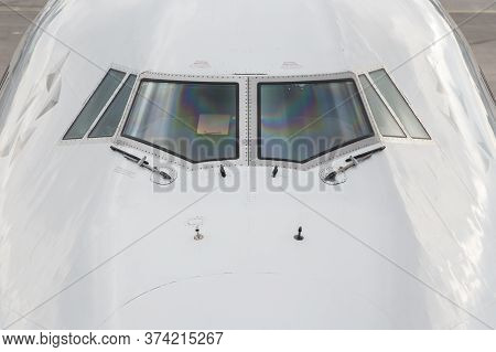 Close Up Of The Front Windshield And Wipers Of A Jumbo Jet With The Airport As A Background.