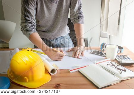 Architect Designing On Table In Office,vintage,sunset Light,yellow Safety Hard Hat