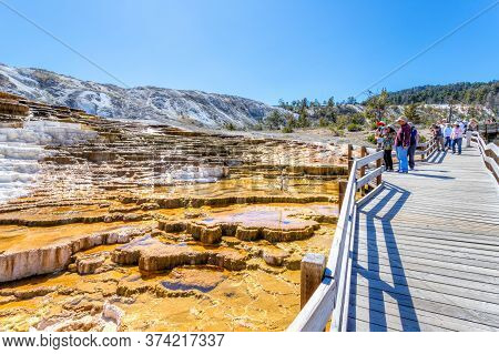 Wyoming, Usa - Aug. 28, 2019: Visitors Admiring Jupiter And Mound Terraces Along The Boardwalk At Ma