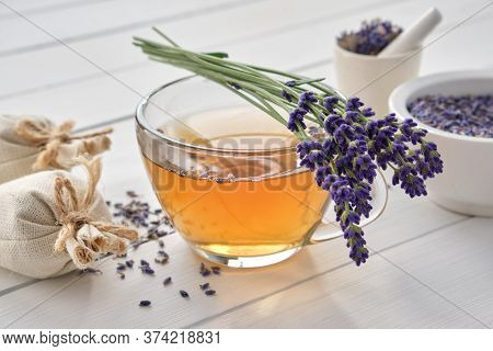Cup Of Healthy Lavender Tea And Lavender Flowers. Mortars Of Dry Lavender And Sachets On Background.