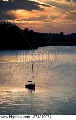 Sunrise On Slezská Harta, A Lone Sailboat On The Water Surface