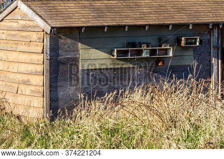 Gray Wooden Shed From Old Boards Outdoors In Dry Grass On A Sunny Day.