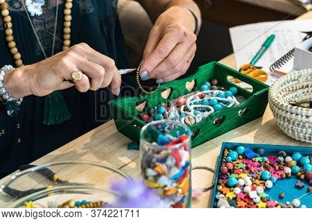 Female Hands Using Pliers To Make A Bracelet Using Metal And Plastic Accessories Working At Her Work