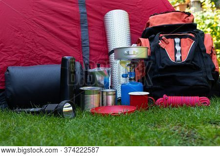 Picture Of Camping Tools On The Grass - Backpack, Tent, Gas Tank, Cans, Compass, Etc - Ready To Go I