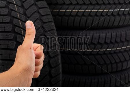 Close Up Picture Of Black New Tyre And Human Hand Showing Thumbs Up