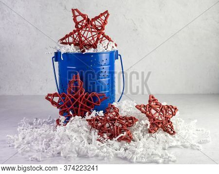 A Blue Bucket With Star Pattern Filled With White Paper Shreds And 3 Red Wooden Stars On A Plaster B