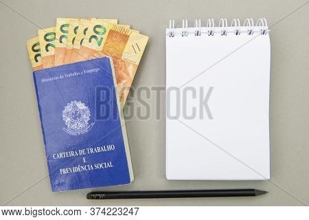 Top View Of Working Card With Money Bills Inside Next To A Notepad On Blank Background. Translate: M