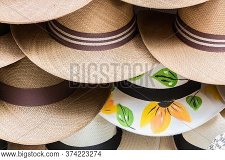 Close Up Of A Group Of Brown Colombian Hats, One Of Them, White With Flowers.