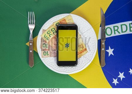 Florianopolis, Brazil June 27, 2020: Top View Of Cellular Over Food Plate Next To Cutlery And Brazil