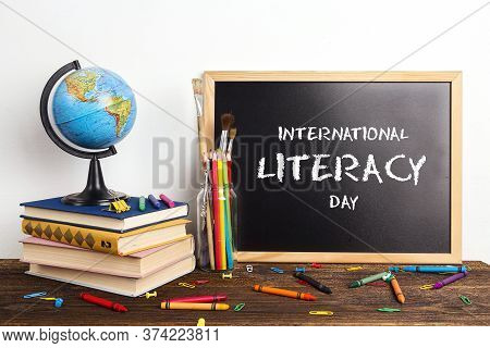 Banner For International Literacy Day With Chalkboard, A Globe, A Stack Of Books And School Supplies