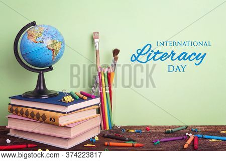 International Literacy Day Composition With A Globe, A Stack Of Books And School Supplies On A Green