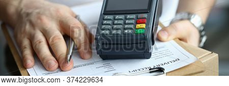 Man Holds Parcel Delivery Document And Terminal. Payment Card Reader. Wireless Portable Terminal For