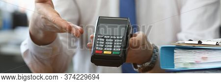 Man Holds His Hand Wireless Terminal For Payment. Bank Employee Offers To Install A Wireless Termina