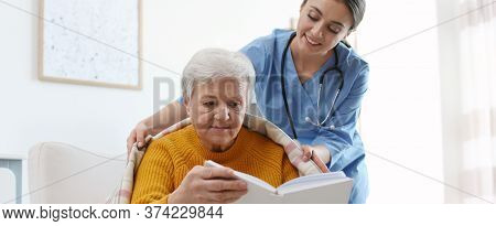 Care Worker Covering Elderly Woman With Plaid In Geriatric Hospice. Banner Design