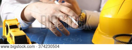 Man Holds Pencil, On Table Yellow Helmet And Truck. Construction Calculation For Use Rented Equipmen