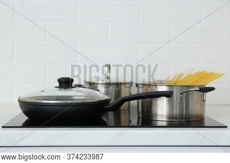 Pot With Uncooked Pasta And Frying Pan On Stove In Kitchen