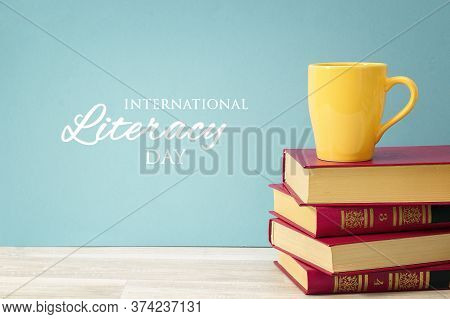 International Literacy Day Concept With Stack Of Books And Yellow Mug Against Blue Background.
