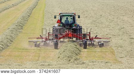 Tractor And Grass Turner Work In Dutch Meadow