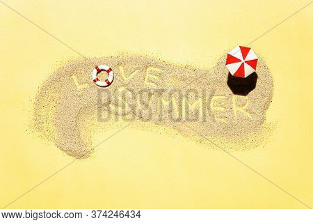 Text Love Summer Written In Sand On A Miniature Beach With A Sunshade Umbrella And A Lifebuoy On A Y