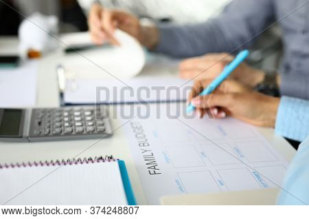Close-up Of People Planning Family Budget. Calculator And Notebook On Table. Earning And Expenses Fo