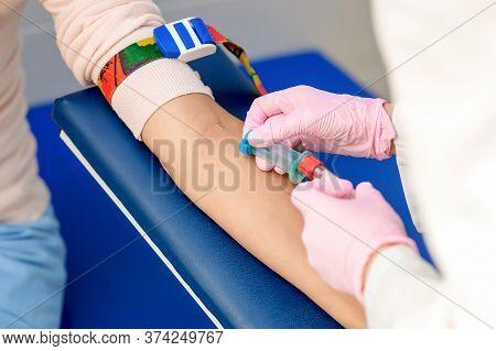 Nurse Introducing The Coronavirus Vaccine Introducing A Needle Into A Vein Of Arm Of Woman.