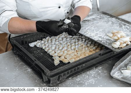 Raw Dumplings.the Process Of Cooking. A Cook In Gloves Sculpts Them.