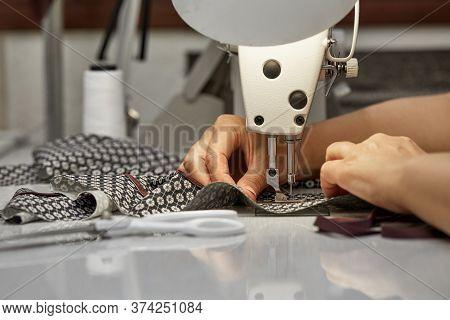 Girl Seamstress Sew On The Sewing Machine. Womens Hands Sewing On The Sewing Machine. Tailoring Proc