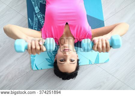 Top View Of Charming Female Sweating In Studio Doing Exercise For Arm. Young Woman Lifting Blue Dumb