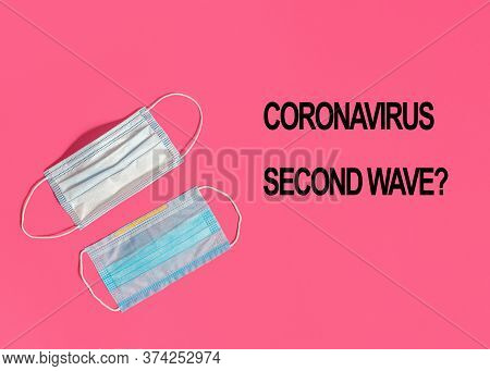New And Used Medical Masks On A Pink Background With The Text Coronavirus Second Wave