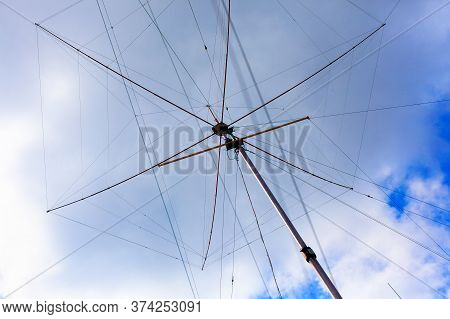 Tall Ham Radio (amateur Radio) Antenna Against Cloudy Sky.