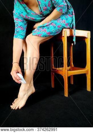 Girl In A Biscay Green-fucsia Bathrobe Makes Hair Removal On Legs Sitting On The Tall Wooden Stool.