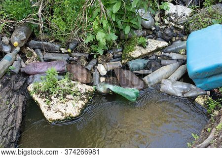 Dirty old plastic bottles and other garbage floating in a river