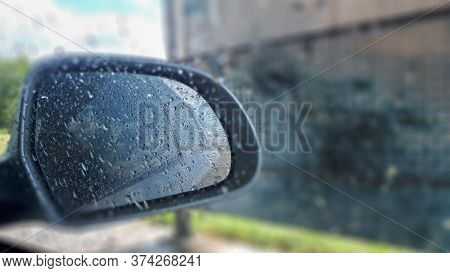 Side Rear-view Mirror On A Modern Car. Water Drop Nature Fresh Wet Background With Water Raindrops.