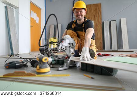Portrait Of Cheerful Smiling Worker Cutting Wooden Laminate. Qualified Male Wearing Yellow Helmet An